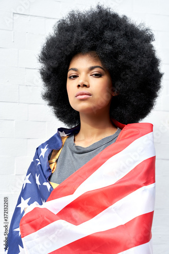 Proud serious young African American woman with Afro hair standing on white background wrapped in usa flag looking at camera outdoor Canvas Print