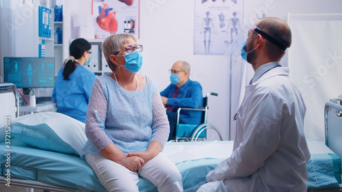 Fotografiet Two old senior persons at doctor wearing masks and talking with nurse and doctor in protective wear