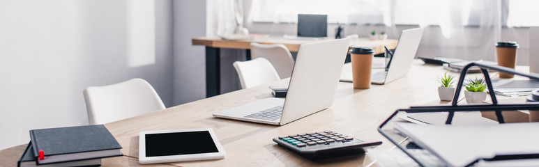 Panoramic shot of notebooks, calculator and digital devices on white office table