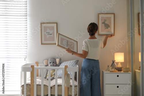 Decorator hanging pictures on wall in baby room. Interior design