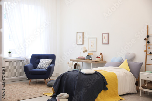 Modern teenager's room interior with bed and armchair Slika na platnu