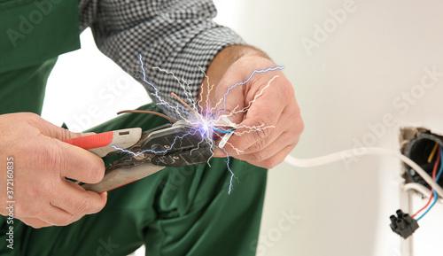 Photo Electrician receiving electric shock while working, closeup