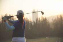 Female Golfer Or Asian Woman Golf Player Doing Golf Swing Tee Off On The Green Sunset Evening Time, She Presumably Does Exercise.