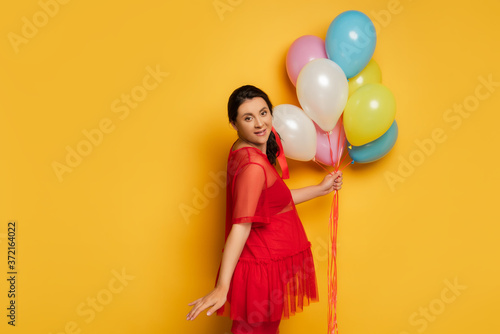 pregnant woman in red tunic holding colorful festive balloons while looking at camera on yellow background