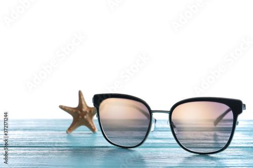 Stylish sunglasses and starfish on light blue wooden table against white backgro Fototapet