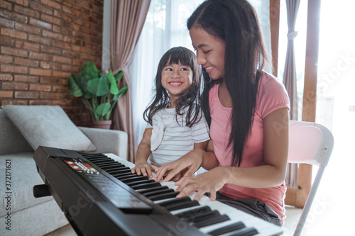 Obraz na plátně two sisters enjoy playing the piano at home doing activities during the pandemic