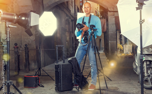 Portrait of male photographer standing with camera among professional photo equi Wallpaper Mural