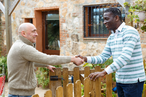 Fotografie, Obraz Friendly farmer greeting his neighbor on courtyard of rural house, shaking hand