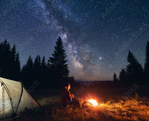 Fototapeta Back view of woman sitting by bright burning campfire near tent alone, enjoying beautiful camping night under dark sky full of stars and bright Milky Way, warm summer evening in the mountains. obraz na płótnie
