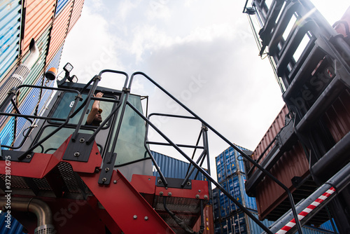 Foreman control loading containers box at cargo warehouse of import and export logistics trade Canvas Print