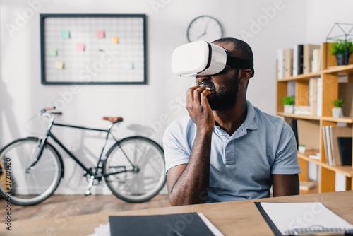 Selective focus of african american businessman using vr headset in office Billede på lærred