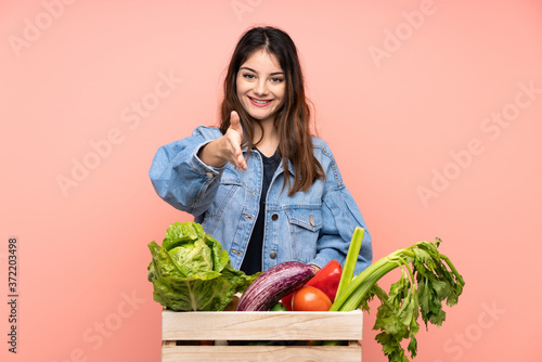 Young farmer woman holding a basket full of fresh vegetables handshaking after g Fototapeta