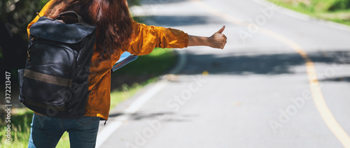 Photo A young female traveler hitchhiking and stopping car with thumbs up on a mountai