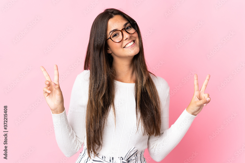 Fototapeta Young brazilian woman isolated on pink background showing victory sign with both hands