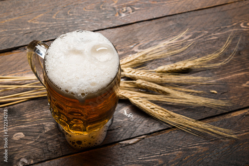 top view of beer pint with foam on wooden table with ears of wheat Fototapete