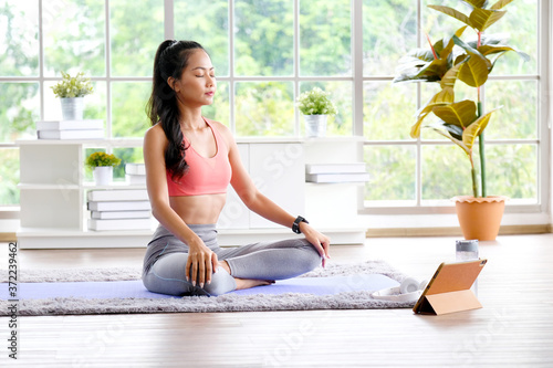 Asian woman practice yoga meditation exercise at home by online training class, Fototapete