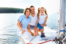 Joyful Family Of Three Posing Smiling To Camera On Yacht