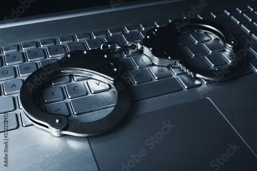 Photo internet fraud cyber crime concept - handcuffs on laptop keybpord
