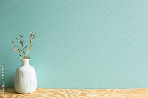 Obraz na plátně Vase of eucalyptus leaves on wooden table with green background