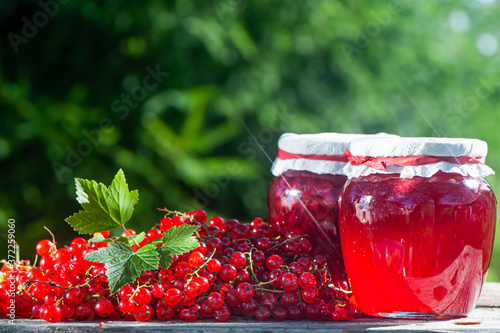 Leinwand Poster Red, juicy berries of red currants and jars of berry jam on a wooden table, on a
