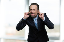 Mature Businessman Making Monkey Face. Caucasian Man In Business Suit Grimacing And Teasing Someone On Blurred Background.