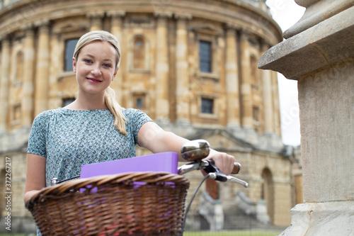 Obraz na plátně Portrait Of Female Student Riding Old Fashioned Bicycle Around Oxford University