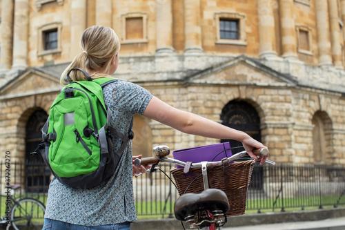 Rear View Of Female Student Riding Old Fashioned Bicycle Around Oxford Universit Slika na platnu