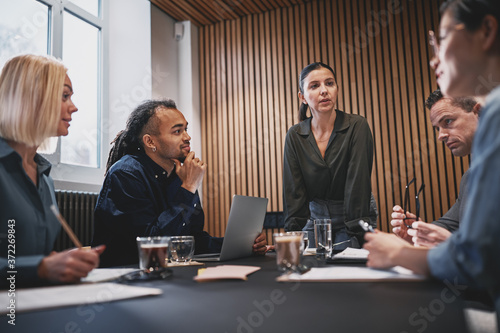 Obraz na płótnie Young businesswoman talking with colleagues during a boardroom m