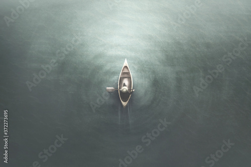 Fotografiet illustration of aerial view of man paddling on a canoe in the water, minimal sum
