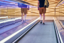 Young Man Goes Down On Moving Walkway In Shopping Center