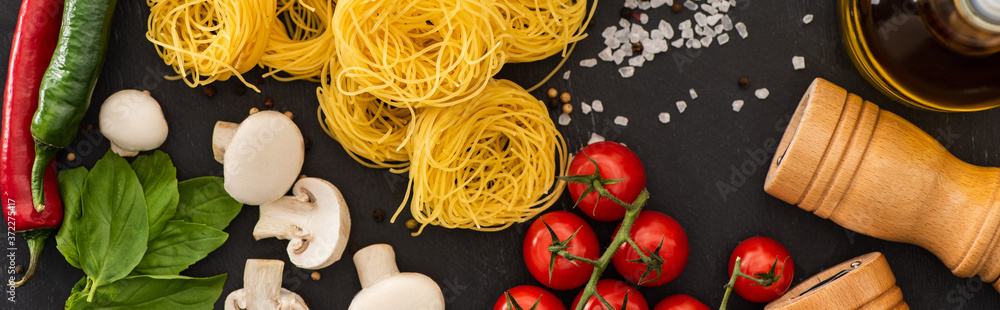 Fototapeta top view of raw Italian Capellini with vegetables and seasoning on black background, panoramic shot