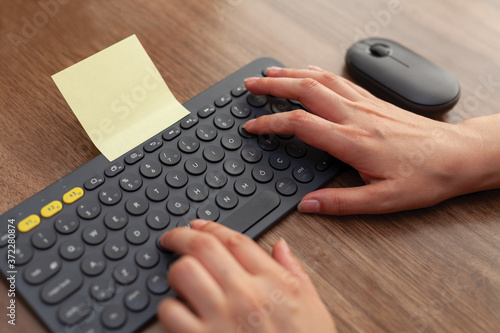 Woman hand touching keys on wireless keyboard and mouse on table Wallpaper Mural