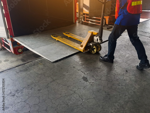 Fotografie, Obraz Worker driving forklift loading shipment carton boxes and goods on wooden pallet