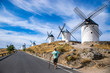 Photo of a middle age man standing next to some beautiful and historic windmills located in Consuegra, Toledo, Spain during a sunny day of summer in a natural place.