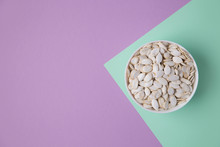White Pumpkin Seeds In A White Bowl On A Green, Lilac Colored Background. The Top View Image Contains Copy Space. Concept Photo