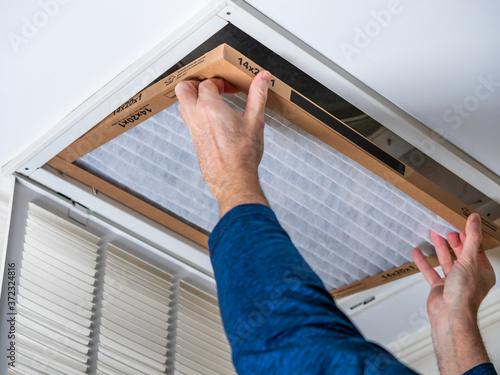 Fotomural Man replacing dirty HVAC air filter in ceiling vent