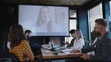 Group Of Multiethnic Business People Using Projector For Online Web Conference Call With Female Coach At Modern Office.