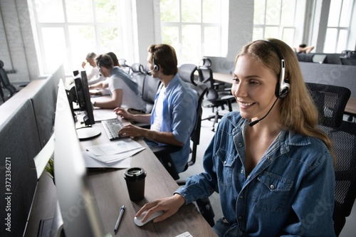Valokuva How can I help you? Beautiful call center workers in headphones are working at modern office