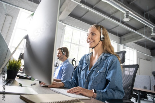Photo How can I help you? Beautiful call center workers in headphones are working at modern office