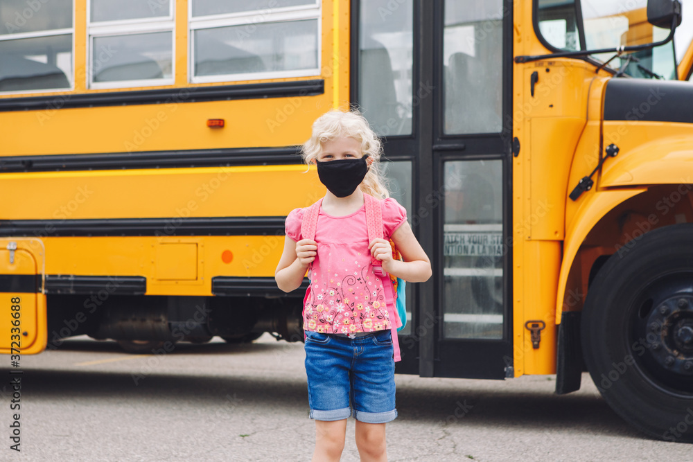 Fototapeta Happy Caucasian girl student wearing face mask near yellow bus. Kid with personal protective equipment on face. Education and back to school in September. A new normal during coronavirus.