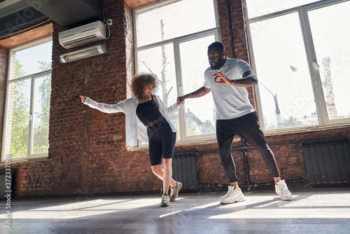 Carta da parati Happy young couple practicing modern dancing in studio
