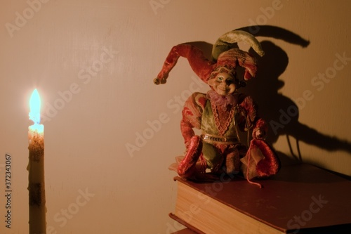 Fototapeta candle light and buffoon doll with shadow on blurry background