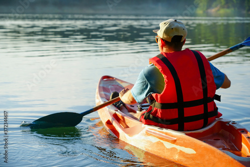 Fototapeta the guy is wearing a life jacket and a cap is floating on the lake in a canoe