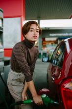 Woman Putting Gas Looking At Camera