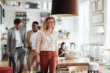 Businesswoman Walking In Cafe Near Colleagues