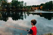 Boy Fishing In Lake In The Fall