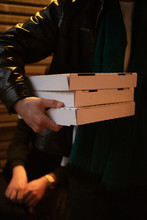 Person Carrying Three Takeaway Pizza Boxes At Night