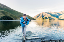 Child Having Fun In The Shallows Of A Mountain Lake