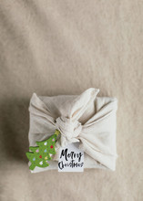 Gift Box Wrapped Inside Rustic Fabric With Wooden Shaped Christmas Tree And A Card Wishing Merry Christmas
