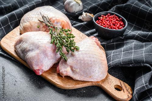 Obraz Fresh chicken thigh with skin on cutting board, organic meat. Black background. Top view - fototapety do salonu